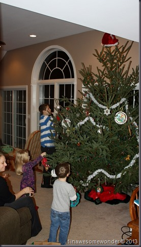 The family is involved, decorating this monster tree.