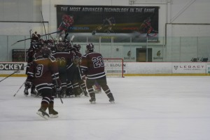 Goffstown celebrates their 4-3 overtime winner. The goal was scored by Captain, Nick Nault. (Photo by Charron)